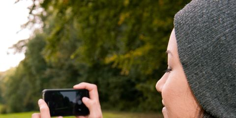 Wrist, Bonnet, Beanie, Gadget, Mobile phone, Knit cap, Long hair, Brown hair, Thumb, Wool,
