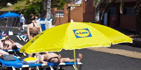 Yellow, Umbrella, Outdoor furniture, Sunlounger, Sun tanning, Swimwear,