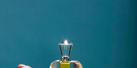Perfume, Turquoise, Cosmetics, Teal, Hand, Liquid, Fluid, Finger, Still life photography, Glass bottle,