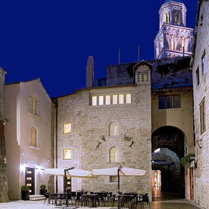 Furniture, Table, Arch, Outdoor table, Kitchen & dining room table, Medieval architecture, Umbrella, Courtyard, Cobblestone, Turret,