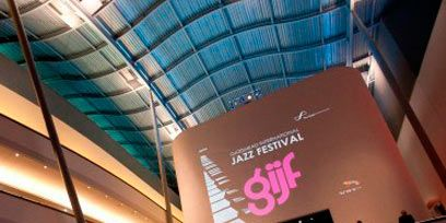 Crowd, Ceiling, Advertising, Display device, Audience, Convention center, Hall, Commercial building, Banner, Daylighting,