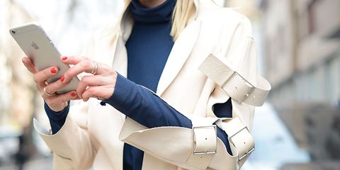 Finger, Hand, Mobile phone, Portable communications device, Street fashion, Communication Device, Blazer, Gadget, Beige, Glove,