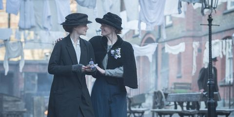 Hat, Coat, Formal wear, Sun hat, Overcoat, Street fashion, Conversation, Fedora, Vintage clothing, Scene,