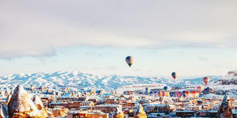 Hot air balloon, Sky, Winter, Town, Snow, City, Urban area, Human settlement, Hot air ballooning, Cloud,