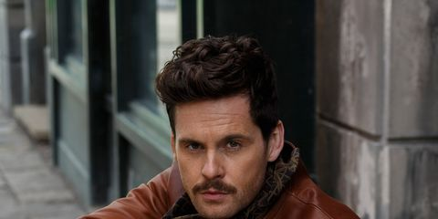 Nose, Facial hair, Sitting, Jacket, Beard, Street fashion, Moustache, Portrait photography, Leather, Natural material,