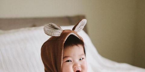 Nose, Comfort, Textile, Facial expression, Linens, Baby & toddler clothing, Costume accessory, Baby, Fawn, Portrait photography,
