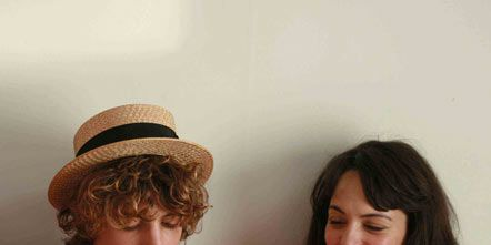 Mouth, Hat, Sitting, Headgear, Sun hat, Necklace, Costume accessory, Fedora, Eating, Kitchen utensil,