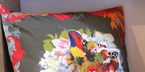 Textile, Orange, Home accessories, Linens, Cushion, Visual arts, Creative arts, Throw pillow, Pillow, Floral design,