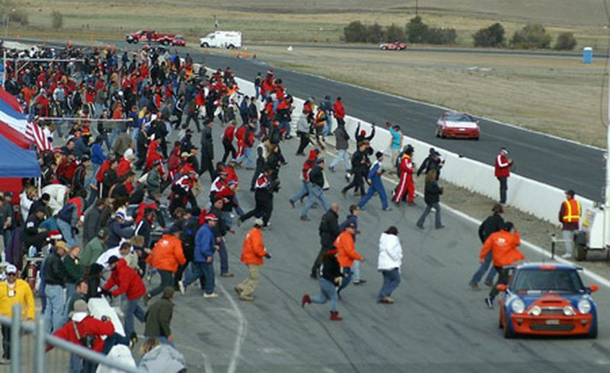 Willows, CA, Dec. 4 - The traditional Rushing of the Wall, like the Running of the Bulls, is a little dangerous, a little heady and more than a little sweaty. The 2005 Thunderhill 25-Hour crews, drivers and assorted rif-raf head for the front straight at the start of the final lap. - Slide 1