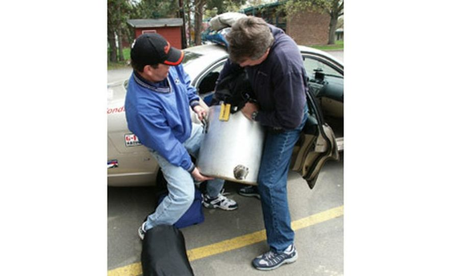 Alternative Fuel class winners Ed Olkkola and Brian Healy wrestle their special trophy - a custom alt-fuel tank surprisingly similar to a commercial kitchen pot - into their Honda Civic Hybrid. Significance? We don't know. - Slide 1