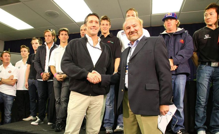 Tony George and Kevin Kalkhoven shake hands amongst drivers and crew at the IRL-CART unification meeting. - Slide 1