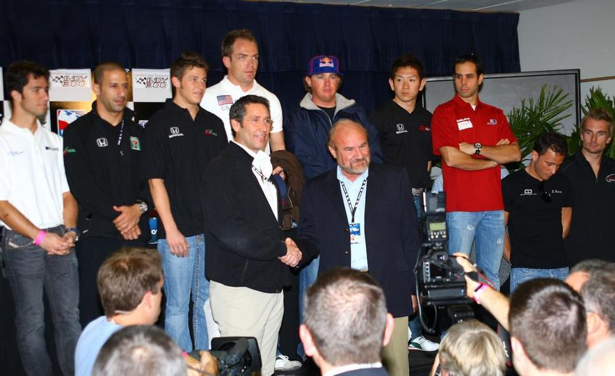 Tony George and Kevin Kalkhoven shake hands amongst drivers and crew at the IRL-CART unification meeting. - Slide 4