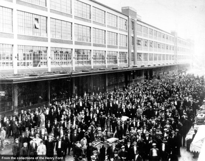 The tedium of moving-assembly-line work proved to be more than many employees could tolerate. Massive turnover prompted Ford to announce the celebrated $5 workday in January 1914. The $5 day, roughly double existing wages, attracted workers from all over the country. Here, an estimated 10,000 applicants brave early January weather in hopes of employment.