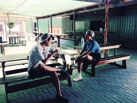 Leg, Human body, Bench, Sitting, Knee, Hardwood, Outdoor furniture, Outdoor bench, Wood flooring, Sandal,