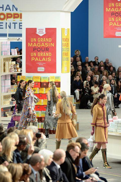 Coat, Logo, Fashion, Jacket, Street fashion, Dress, Shelf, Luggage and bags, Advertising, Boot,