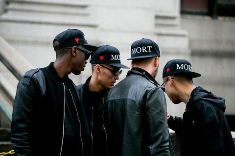 Cap, Jacket, Outerwear, Baseball cap, Interaction, Headgear, Street fashion, Leather jacket, Cricket cap, Leather,