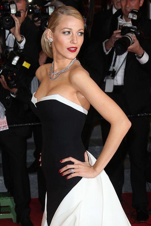 Trousers, Single-lens reflex camera, Dress, Camera, Red, Outerwear, Premiere, Style, Film camera, Fashion accessory,