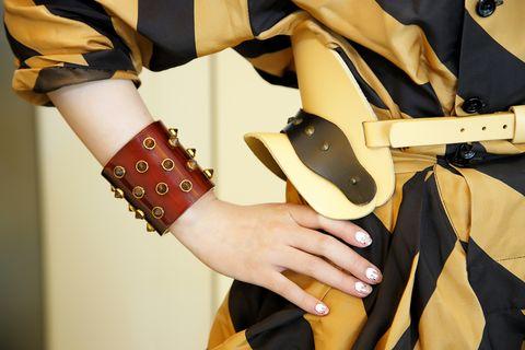Wrist, Orange, Nail, Bag, Waist, Thumb, Fashion design, Cuff, Abdomen, Leather,