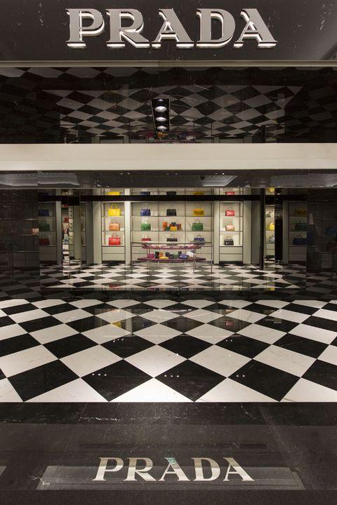 Floor, Flooring, Tile, Commercial building, Logo, Signage, Concrete, Retail, Symmetry, Tile flooring,