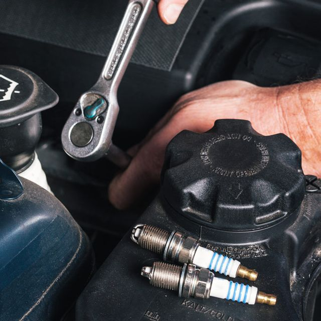 Mechanic is unscrewing the ignition plugs of a modern car