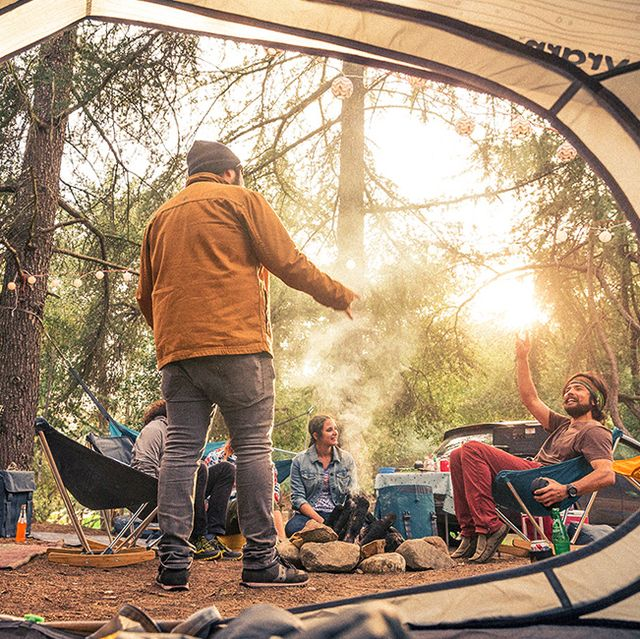 the view from inside a tent of a group of people sitting around a stone fire pit