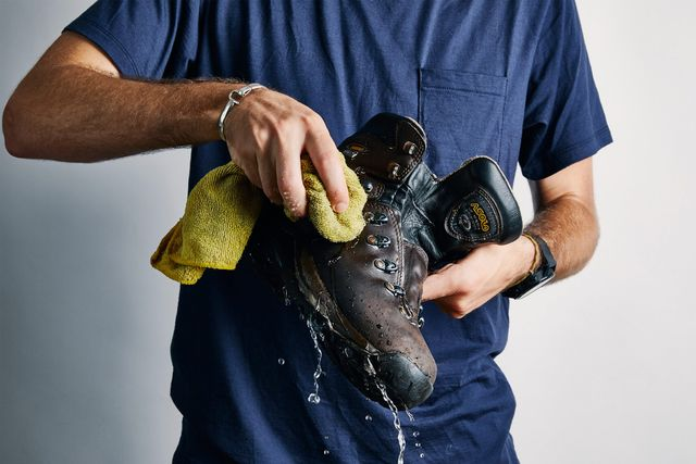 a person washing a leather hiking boot