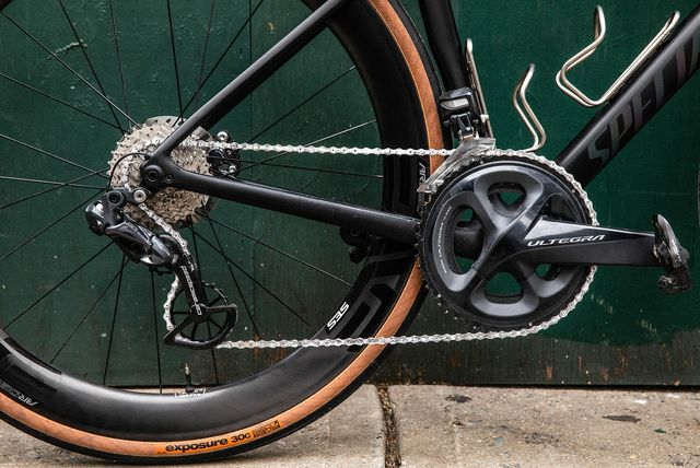 a close up of the gears, chain, derailleur, rear wheel and pedals of a black bicycle