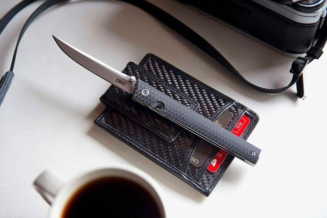 a slim folding pocket knife atop a black wallet on a table next to a cup of coffee