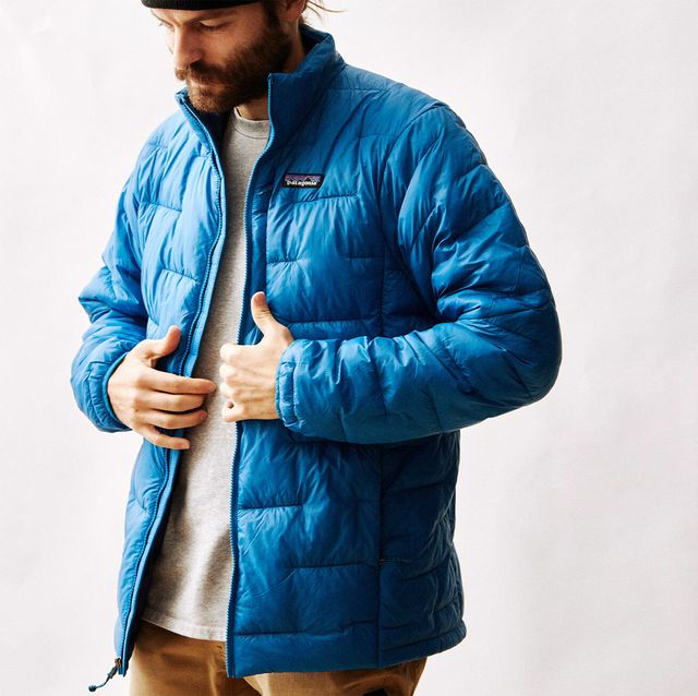 a man wearing a blue patagonia puffy jacket on a blank background