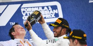 Lewis Hamilton pours Champagne on Mercedes chief engineer Fred Judd on the podium.