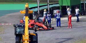 Course workers remove the damaged car of Sebastian Vettel in Brazil on Sunday.