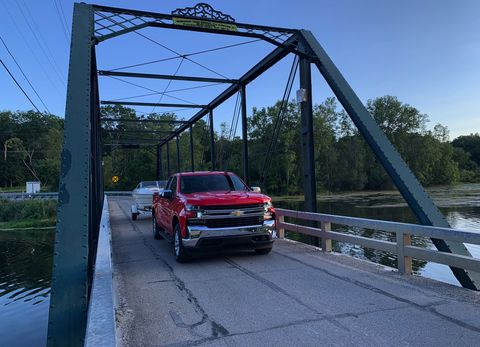 the 2019 chevrolet silverado stands triumphant on a small wrought iron bridge outside of ann arbor, michigan, near its final destination after towing a boat nearly 250 miles