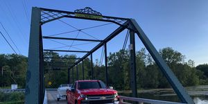 The 2019 Chevrolet Silverado stands triumphant on a small wrought-iron bridge outside of Ann Arbor, Michigan, near its final destination after towing a boat nearly 250 miles.
