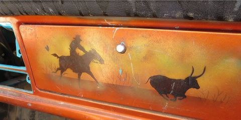 The glovebox lid features a heroic Colorado cowboy pursuing a longhorn bull.