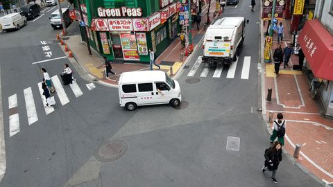 A Honda Acty follows a garbage truck in Shinjuku.