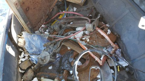 In addition to several spare fenders in front, the trunk is full of parts.