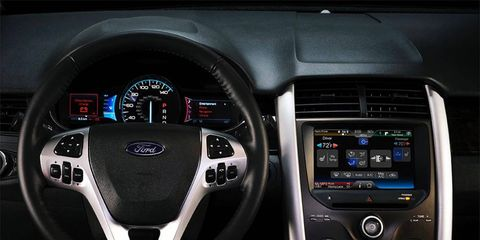 The MyFord Touch control and display system includes video display screens that flank the speedometer and a screen in the center stack.