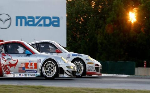 The Flying Lizards Motorports Porsche 911GT3 RSR moves inside of the 911 Design Porsche 911 GT3 Cup car as evening sets in at the Petit Le Mans.