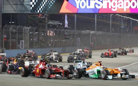 2012 Singapore Grand Prix: Paul di Resta, Force India VJM05 Mercedes, leads Fernando Alonso, Ferrari F2012, Mark Webber, Red Bull RB8 Renault, and the remainder of the field through the first corner.