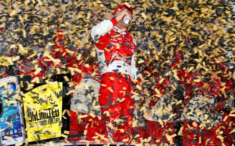 Kevin Harvick enjoys a Budweiser in a sea of confetti at Kansas Speedway after his win on Sunday.