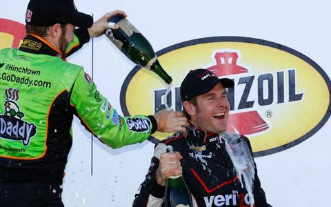 Will Power gets doused in champagne by James Hinchcliffe after Sunday's IndyCar race in Houston.