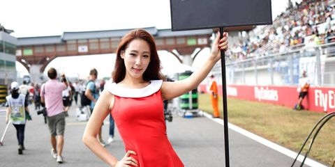 Despte all the commotion in the pits before the Formula One Korean Grand Prix, this grid girl keeps her focus.