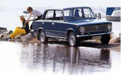 A couple and their Lada relax by the water