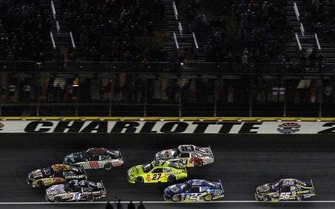 A pack of cars battles for position around Charlotte Motor Speedway. Photo by: LAT Photographic