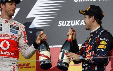 First-place Jenson Button (left) and third-place Sebastian Vettel (right) celebrate their success in the Japanese Grand Prix. Photo by: Andrew Ferraro/LAT Photographic