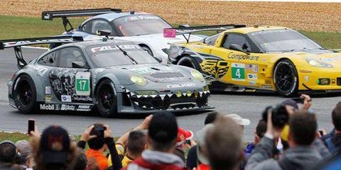 The Team Falken Tire Porsche 911 GT3 RSR and Corvette Racing Chevrolet Corvette C6 ZR1 battle for position as  fans record the opening laps of  the Petit Le Mans in Braselton, Ga., on Oct. 19.