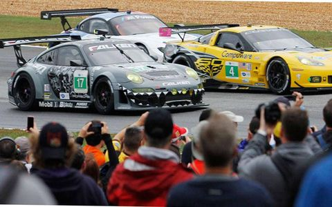 The Team Falken Tire Porsche 911 GT3 RSR and Corvette Racing Chevrolet Corvette C6 ZR1 battle for position as  fans record the opening laps of  the Petit Le Mans in Braselton, Ga., on Oct. 19.
