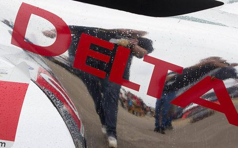 Fans are reflected in the chrome finish of the DeltaWing prior to the start of the Petit Le Mans at Road Atlanta.