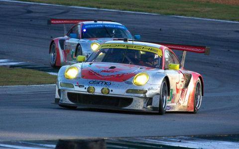 The Flying Lizard Porsche 911 GT3 RSRs run together through turn 10b.