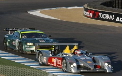 An Aston Martin DBR9 chases an Audi R10 down the Laguna Seca front straight during practice.